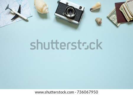 Items for summer vacation: a camera, passport, money. Blue background, top view. Copy space.