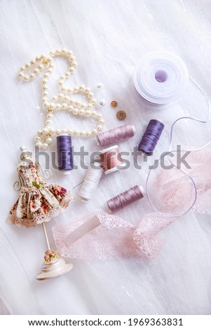 Items for tailoring - spools of thread, needles, ribbons, lace, buttons, pearl necklace on a background of tulle with sequins. Foto stock ©