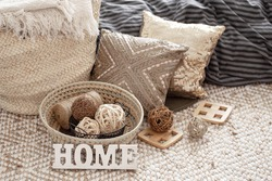 Items of a cozy home interior with pillows and a wooden sign home .Coziness and comfort at home .
