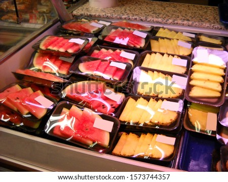 Items on display in a store window. Portioned packages by weight of fruit. Pieces of watermelon and pineapple, packaged in plastic packaging - containers, and wrapped in sticky cling film. #1573744357
