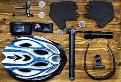 Items replacements and tools for a safe cycling: Helmet, gloves, glasses, pumps, patches, tire, chain tool, flat lay. Top view.. Tools and accessories set for cycling