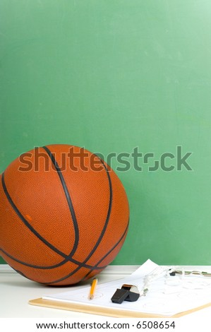 Items used by a basketball coach including a ball and a black board with copy space