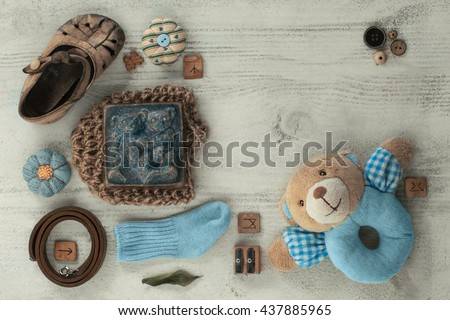 Its a Boy Baby Shower or Nursery layout with soap, booties, socks on pale white shabby chic table