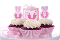 Its a Girl Baby Shower Cupcakes with baby feet toppers and decorations on shabby chic pink wood table.
