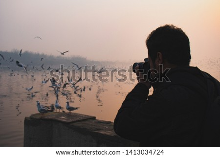 Its a picture of a photographer at a river bank clicking pictures of birds