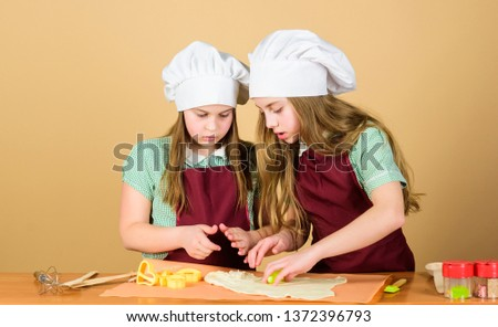 Its not the gods who bake pots. Small children rolling paste to bake pies. Adorable little girls preparing dough in bake shop. Cute kids learning to bake bread. #1372396793