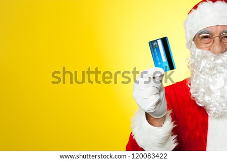 Its shopping time. Cropped image of aged Santa holding credit card.