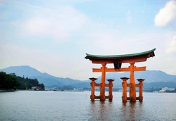 Itsukushima shinto torii on the water, with the city and mountains behind, Miyajima Island, Japan