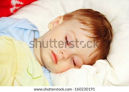 ittle baby asleep in bed, his head on the pillow close-up.