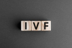 IVF - acronym from wooden blocks with letters, abbreviation IVF In vitro fertilisation concept, gray background