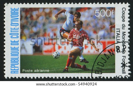 IVORY COAST - CIRCA 1990: stamp printed by Ivory Coast, shows Soccer players and ball, circa 1990.