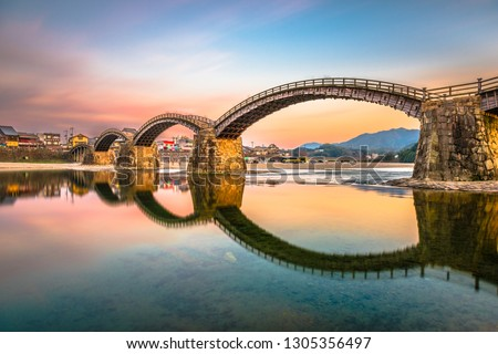 Iwakuni, Yamaguchi, Japan at Kintaikyo Bridge over the Nishiki River at dusk.