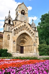 Ják Chapel with flowers in the foreground  - church in City Park, Budapest opposite Vajdahunyad Castle, small romanesque chapel, intricate facade decorated with geometric and religious statues