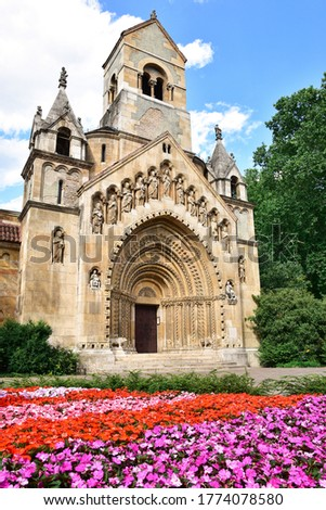 Ják Chapel with flowers in the foreground  - church in City Park, Budapest opposite Vajdahunyad Castle, small romanesque chapel, intricate facade decorated with geometric and religious statues Foto d'archivio ©