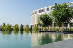 Jacaranda (Jacaranda mimosifolia) trees in fountain 'Infinity' in form of huge bowl with granite steps on Stadium Krasnodar background. Public landscape park 'Krasnodar' or 'Galitsky park'