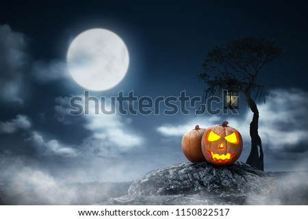 Jack-o-lantern above the rock with lantern hanging on the branch at night. Halloween background #1150822517