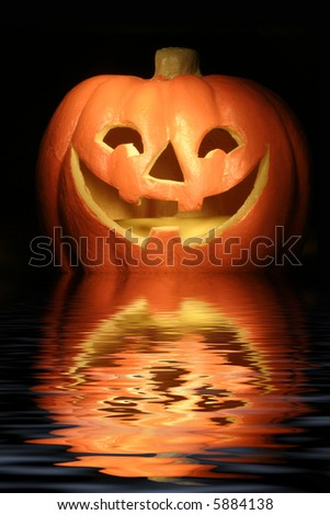 jack-o-lantern against a dark background with reflection