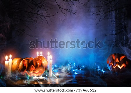 Jack o lantern in blue moonlight. Halloween background. Pumpkins Burning In A Spooky Forest At Night #739468612