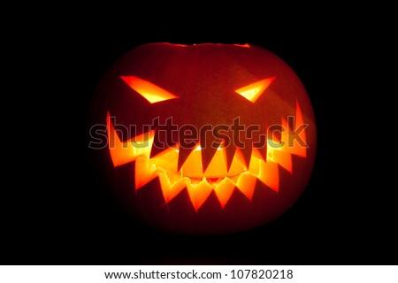 Jack-o'-lantern, smiling Halloween pumpkin glowing in the night.