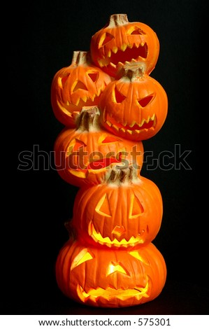 Jack O Lanterns - a stack of pumpkins carved into lighted jack-o-lanterns over black background for Halloween.