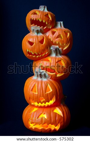 Jack O Lanterns - a stack of pumpkins carved into lighted jack-o-lanterns over deep blue background for Halloween.