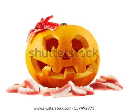 Jack-o'-lanterns pumpkin with a spider and teeth shaped sweets around it, isolated over white background