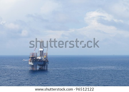 Jack up drilling rig and crew boat in the middle of the coean