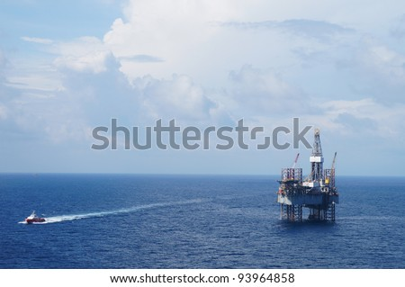 Jack up drilling rig and crew boat in the middle of the ocean