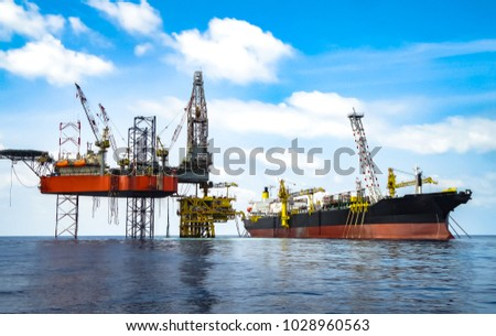 Jack up drilling rig on production platform with FPSO on site