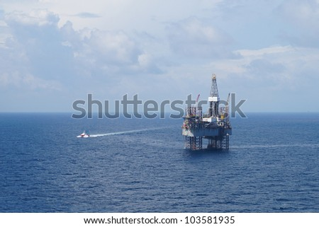 Jack up oil drilling rig and a crew boat in the middle of the ocean