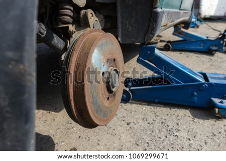 jacked up car with a movable lifter, for changing the tire or brake disk #1069299671