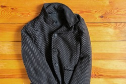 jacket with peas female black lies on a wooden table close-up, women's clothing, jacket with peas