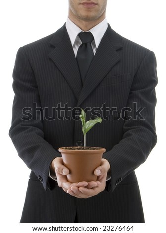 Jacketed and tied business man offering a plant in a terracotta vase