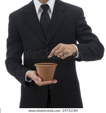 Jacketed and tied business man seedling a terracotta vase with green palant - stock photo