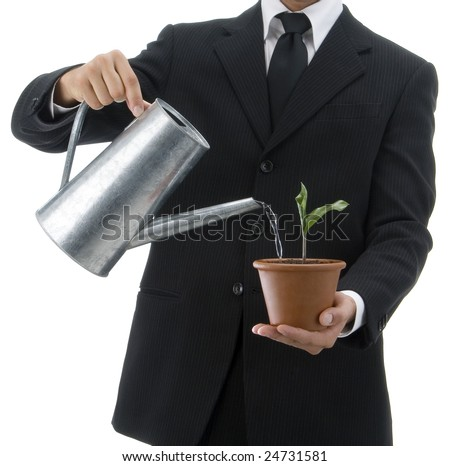 Jacketed and tied business man with a watering-can watering a terracotta vase with green palant