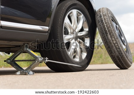 Jacking up a car to change a tyre after a roadside puncture with the hydraulic jack inserted under the bodywork raising the vehicle and the spare wheel balanced on the side