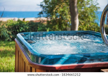 Jacuzzi close up focus in the water with a blurry garden and sea view background  Photo stock ©