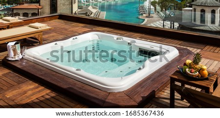 Jacuzzi on the terrace of a Luxury Hotel, wine glasses and fruit platter. Spa complex, vacation and traveling concept Photo stock ©