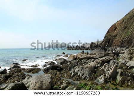 Jagged, dramatic rocks on a coastline with a bright blue sea, in Pembrokeshire, Wales