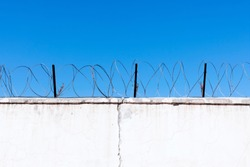 Jail wall. Highly protected prison wall with barbed wire fence. Blue sky background with copy space