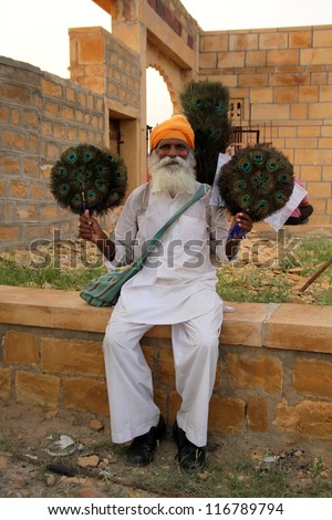 JAILSAMER - INDIA- SEPT 17: Old man sells handmade peacock fans.  World Bank stated, 32% of the total Indian people fall below international poverty line of US$ 1.25 per day on sept 17, 2012 in INDIA - stock photo