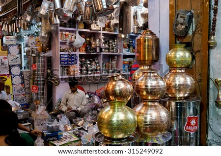 Jaipur, India; 2nd Nov 2013: Metal items and utensils shop with the store owner sitting. These metal retailers and manufacturers do brisk business on the hindu festival of Dhanteras