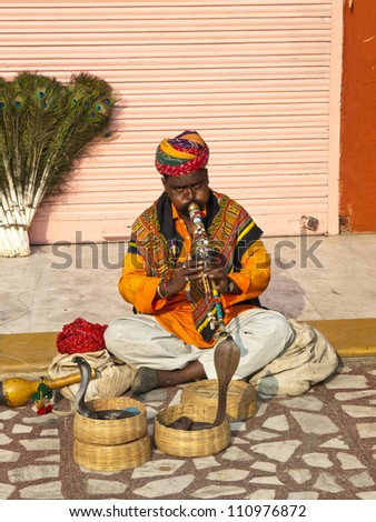 JAIPUR, INDIA - NOVEMBER 7 :Snake charmer shows his skill with the cobra to the tourists in front of the Hawa Mahal in Jaipur, Rajasthan, India on Nov 7, 2009.