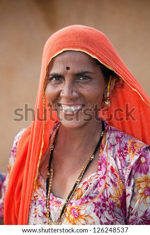 JAISALMER, INDIA - AUGUST 12: Indian woman on Thar desert on August 12, 2011 in Jaisalmer, India. About 40% of the population of Rajasthan live off the agriculture and animal husbandry in Thar desert