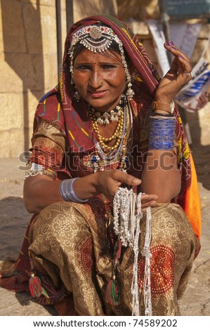 JAISALMER, INDIA - FEBRUARY 3: Unknown Indian lady in traditional outfit selling silver necklaces on February 3, 2007 at Jaisalmer Fort during the annual Desert Festival in Rajasthan, India