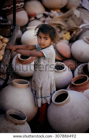 JAISALMER, INDIA - MARCH 22 : Little girl posing in the street on March 22, 2014 in Jaisalmer, India