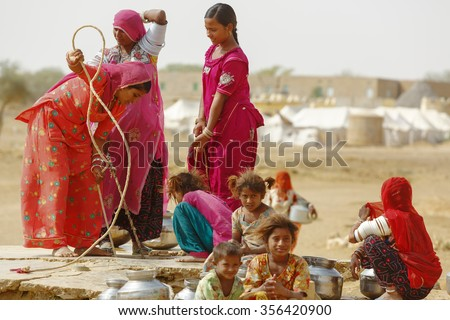 Jaisalmer, India - November 9, 2014 : Unidentified women and children draw water from the draw well and carry the pots to their village near Thar desert, Jaisalmer, Rajasthan, India
