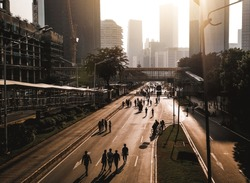 Jakarta in early morning. Shadows and silhouettes of people at a city during Car free day.