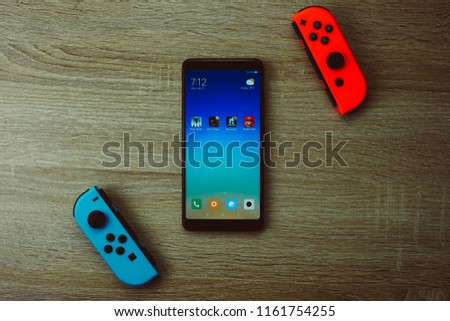 Jakarta, Indonesia - August 22, 2018: The Xiaomi Redmi Note 5 with Joy-Con controller Nintendo Switch and play games: PUBG Mobile, Life is Strange, Lineage 2 Revolution, and Super Mario Run. #1161754255