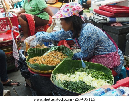 JAKARTA- INDONESIA JANUARY 11, 2015. The local  market, with colourfully dressed people. On the site, people sitting on chairs and eating  meals purchased on the market.